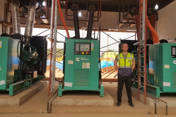 Adem Ersoy, Project Engineer at Cummins Turkey's authorized distributor Mepa Energy, stands next to the standby power system at Kigali Arena.